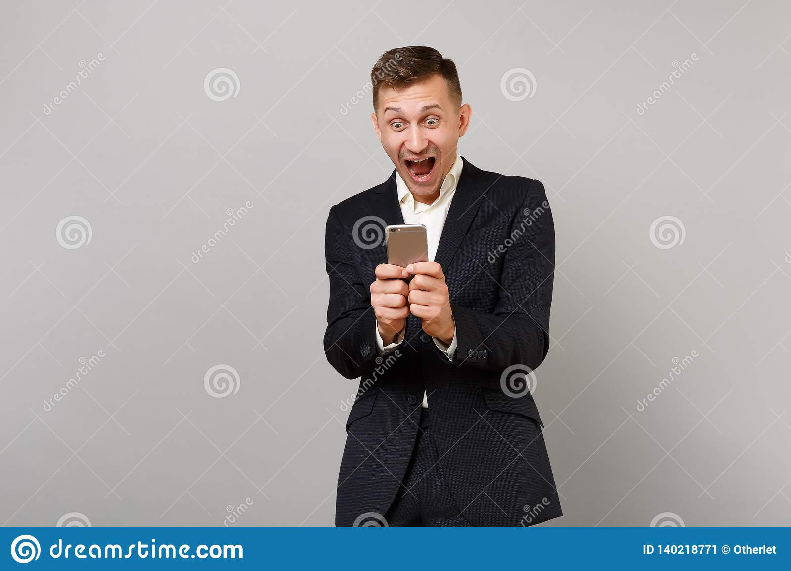 Surprised happy young business man screaming keeping mouth open wide, using mobile phone typing sms message isolated on