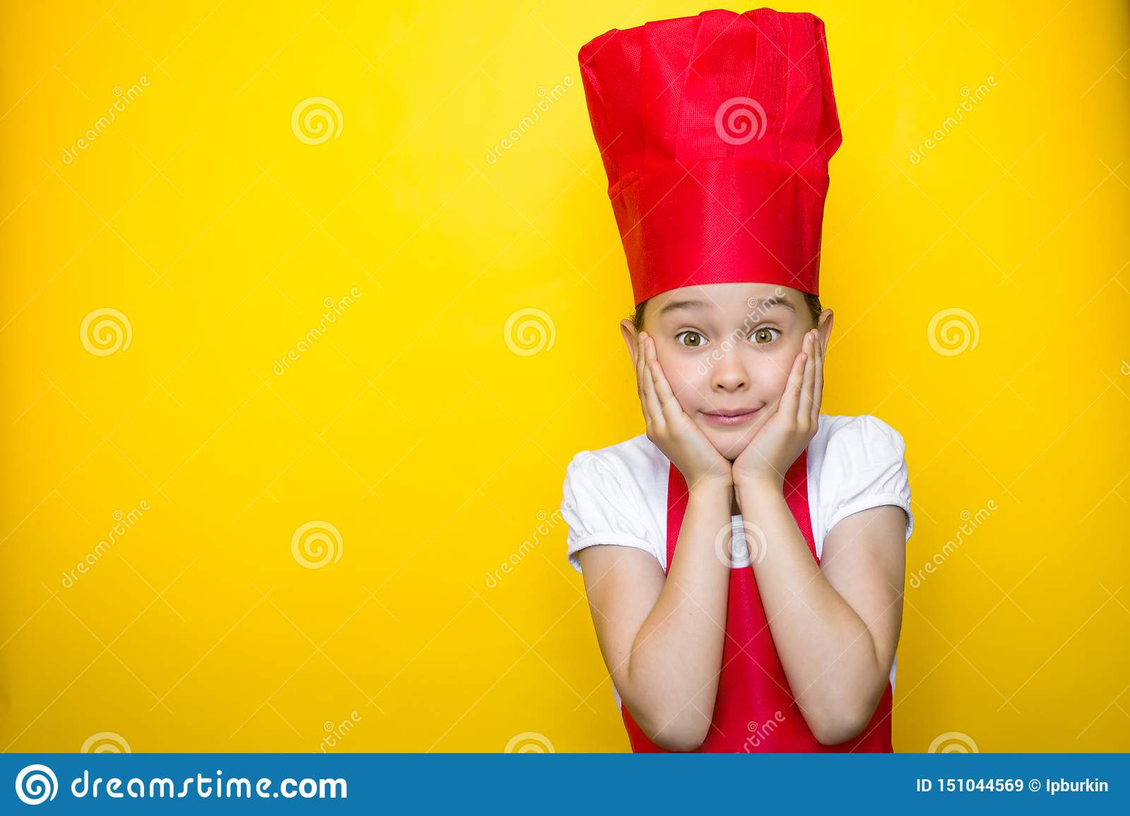 Surprised little girl in a red chef`s suit with hands on cheeks on yellow background with copy space