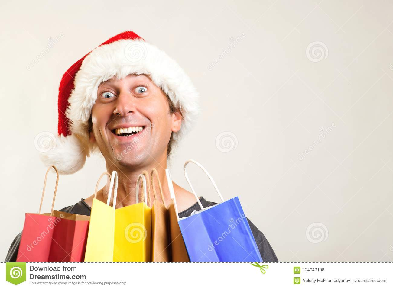 Surprised man in Christmas hat holds shopping bags, isolated on white. Christmas shopping and sales concept. Christmas discounts.