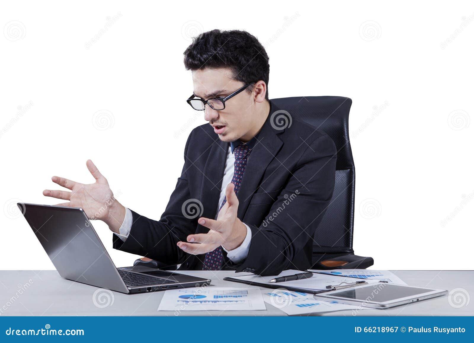 Surprised middle eastern worker looking at laptop