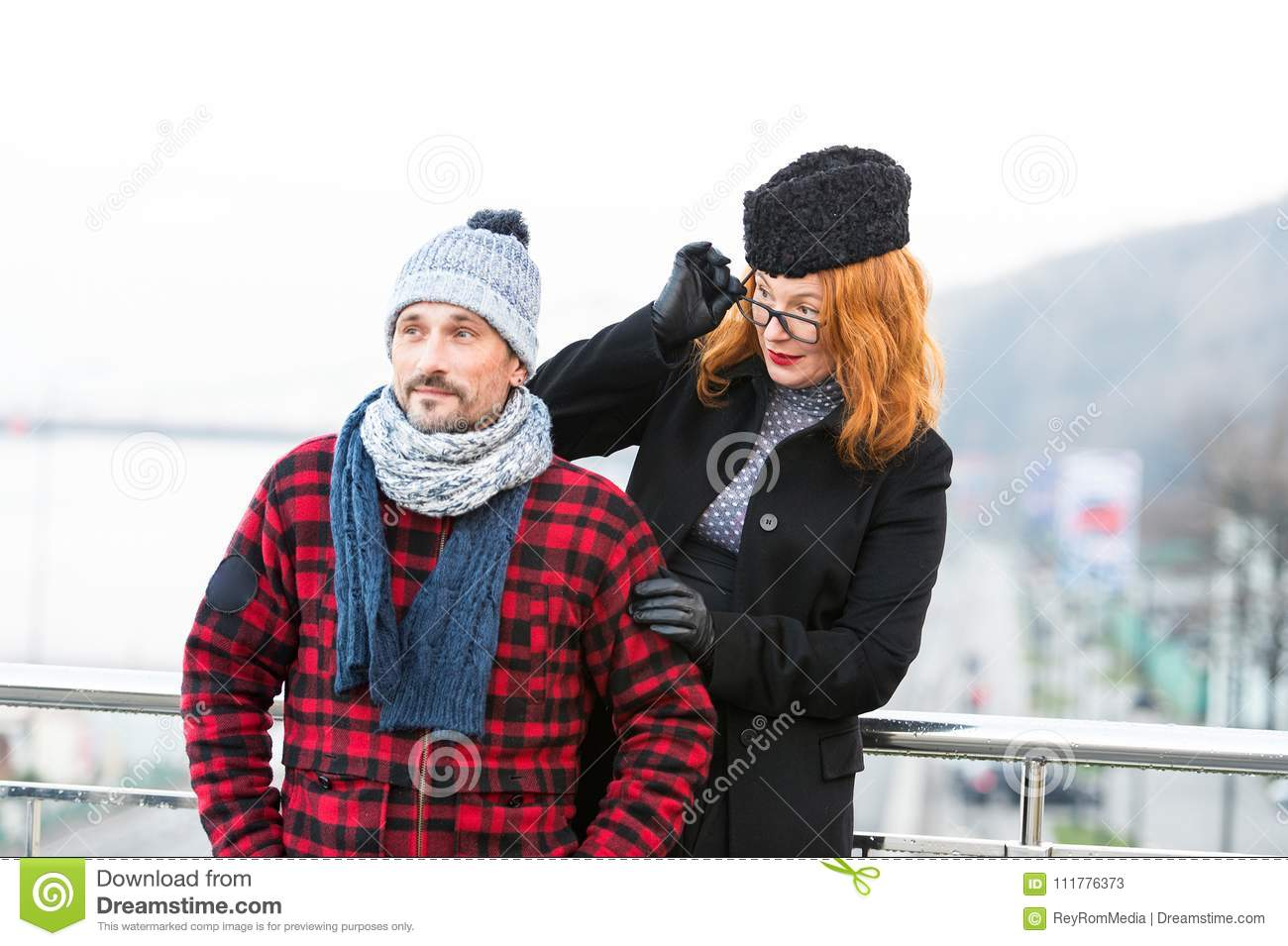 Surprised red hair woman in glasses looked at stranger on bridge. Woman look over the glasses from the man back.