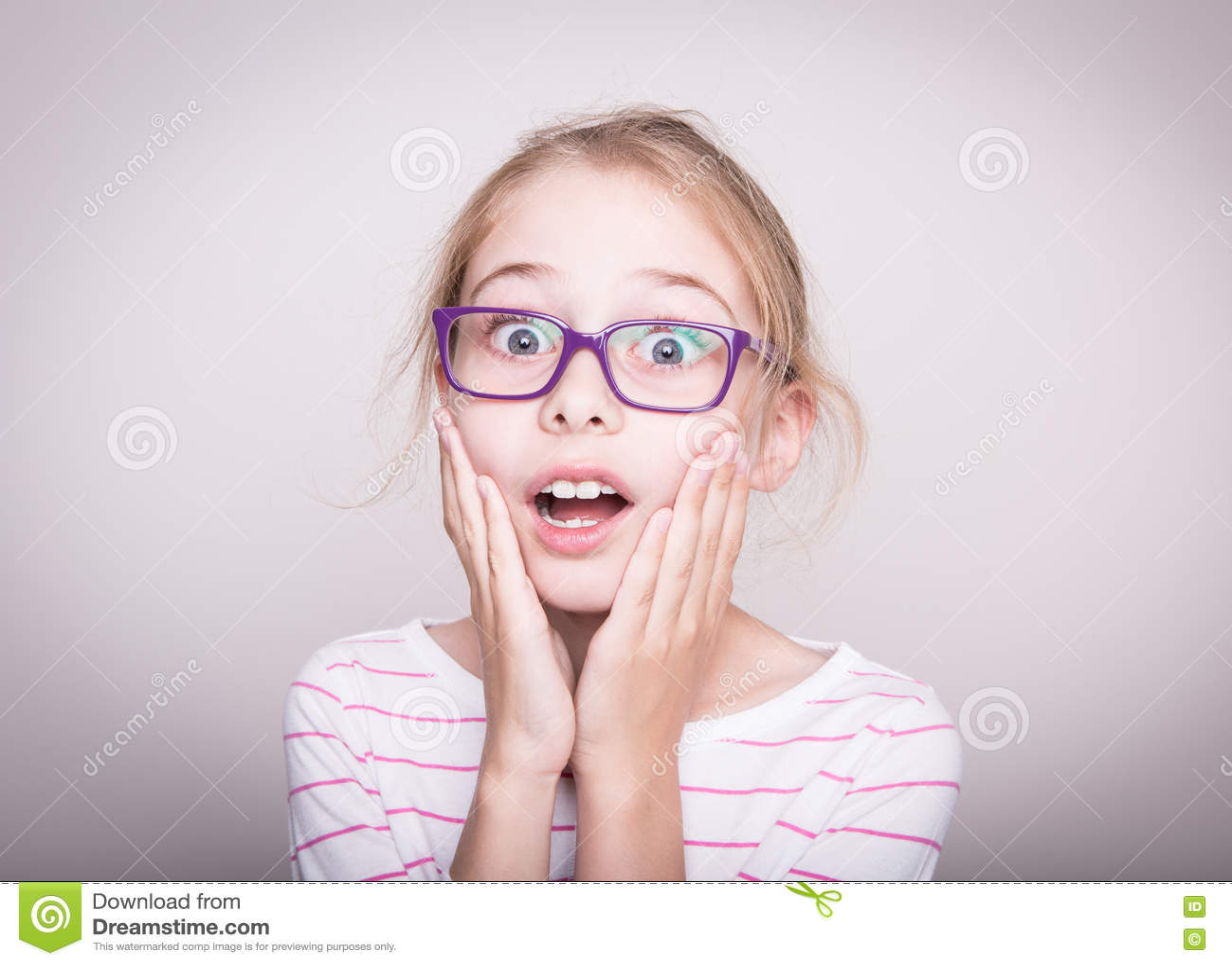 Surprised or shocked face of child girl in violet glasses