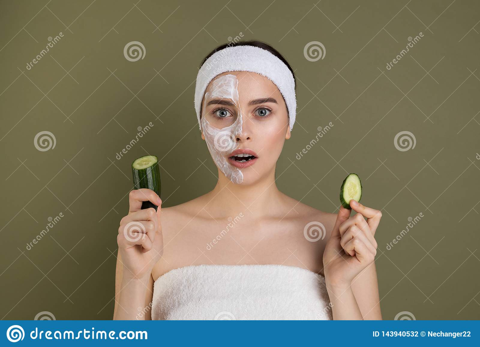 Surprised woman with bare shoulders loking at camera with open mouth, white mask on half of her face