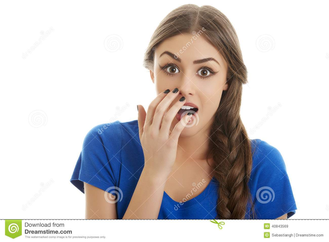 Young scared teenage girl covering her mouth with hand. Isolated on white background stock photography