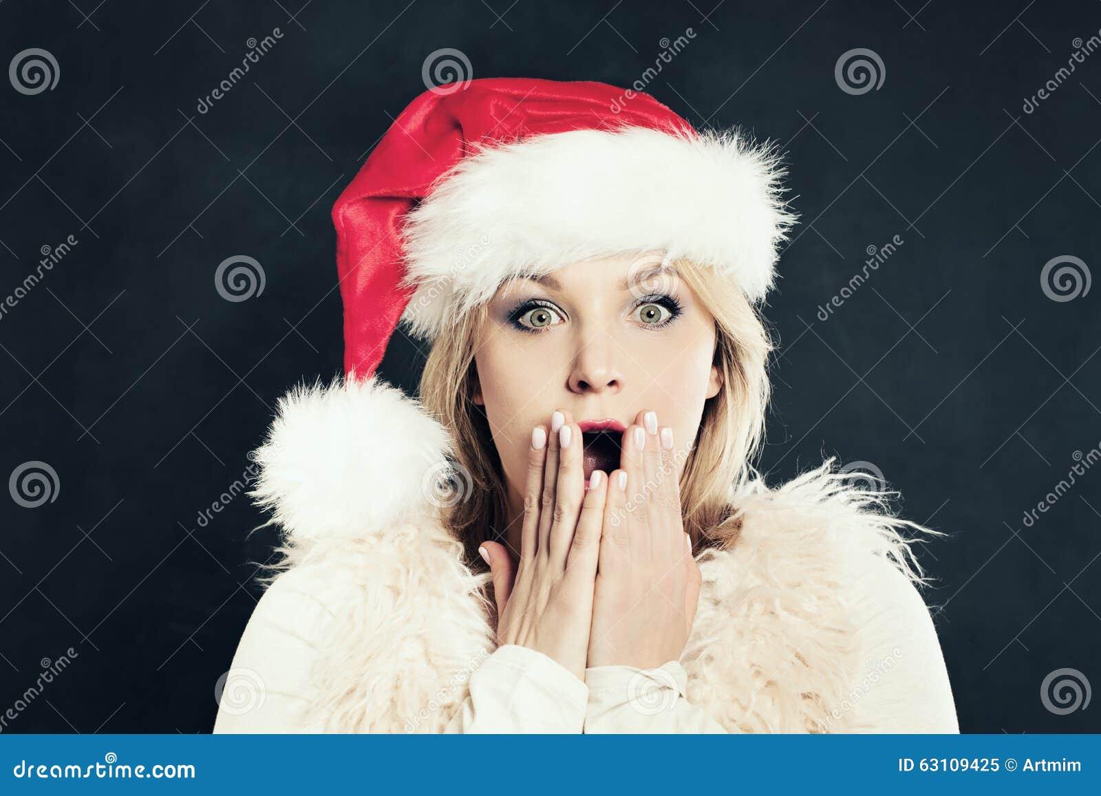 Surprised woman in santa hat having fun christmas sale