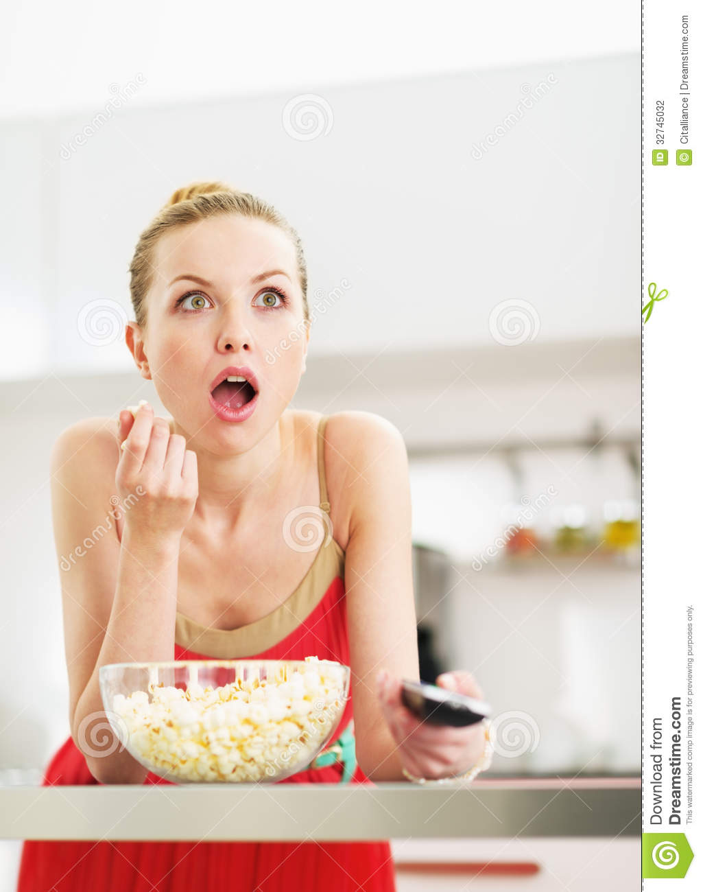 surprised-young-woman-eating-popcorn-wat