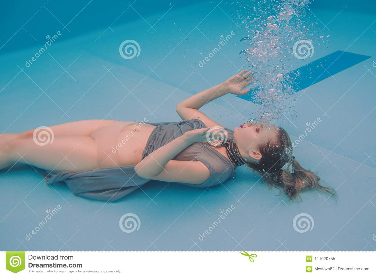 263f19250b Surreal art portrait of young woman in grey dress and beaded scarf  underwater in the swimming pool
