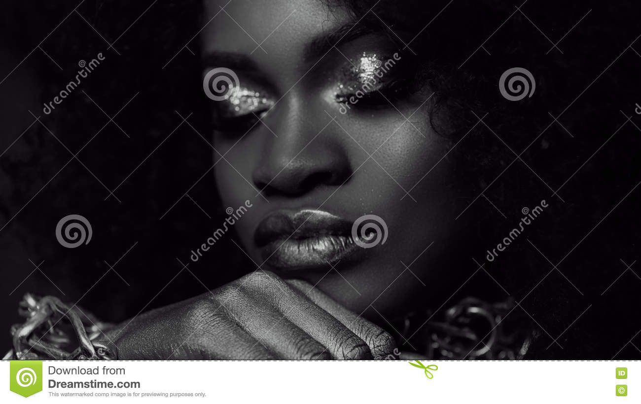 Surreal black and white close-up portrait of young african american female model with gold glossy makeup. Face art