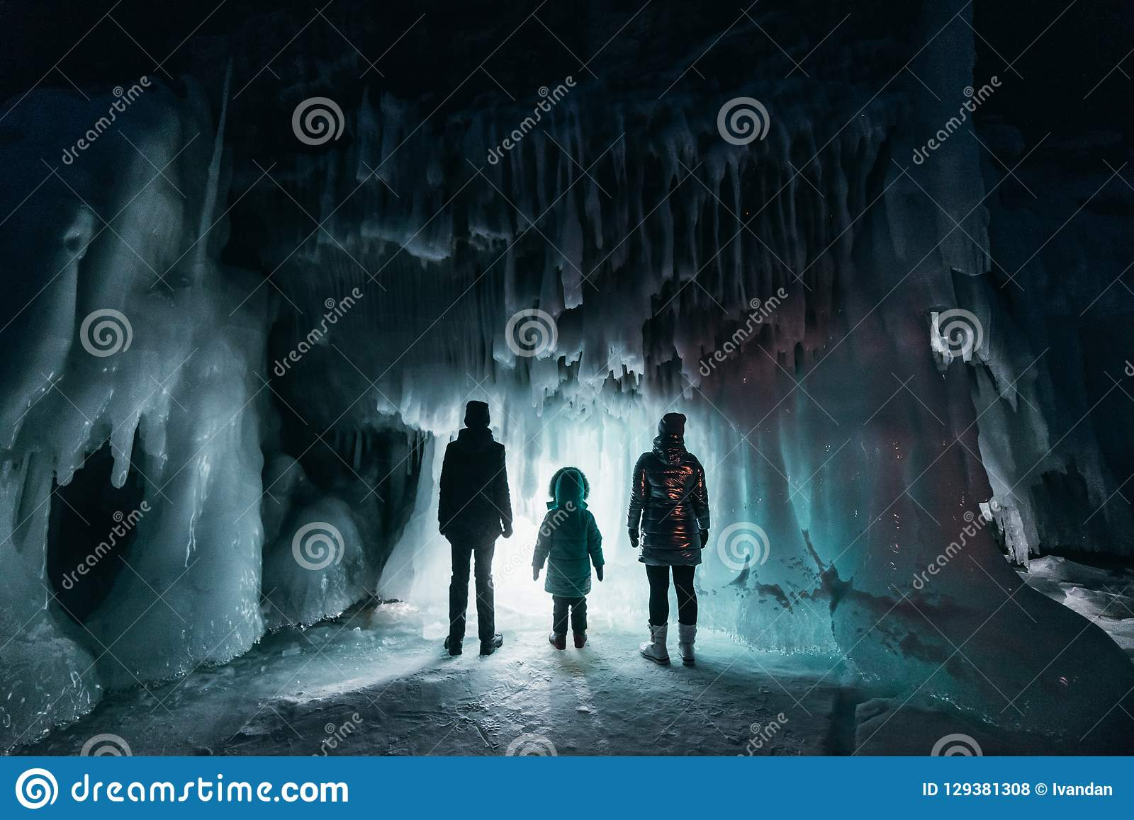 Surreal landscape with people exploring mysterious ice grotto cave. Outdoor adventure. Family exploring huge icy cave