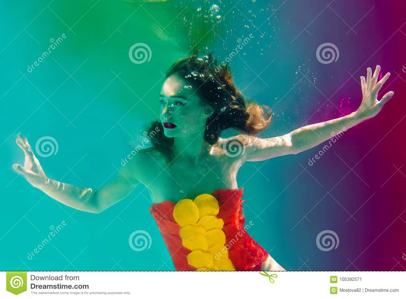 Surreal portrait of young attractive woman with air bubbles underwater in colorful water with ink