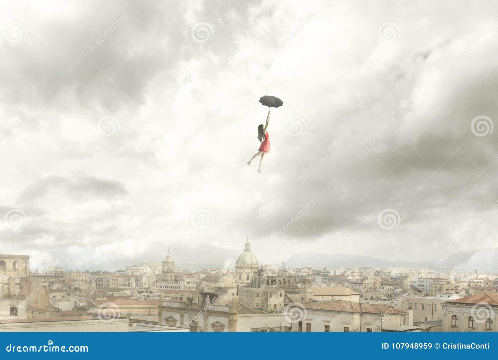 Surrealistyczny moment kobiety latanie z jej parasolem nad miastem
