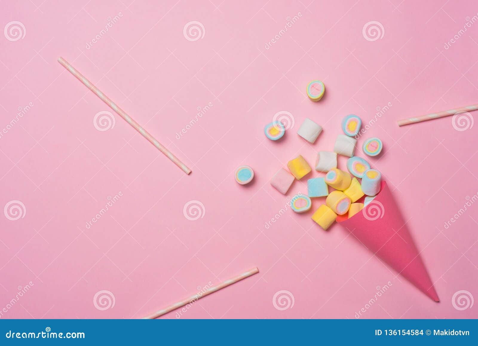Surtido colorido del caramelo de la melcocha en un cono de helado en el fondo rosado visto desde arriba Variación gomosa del cara