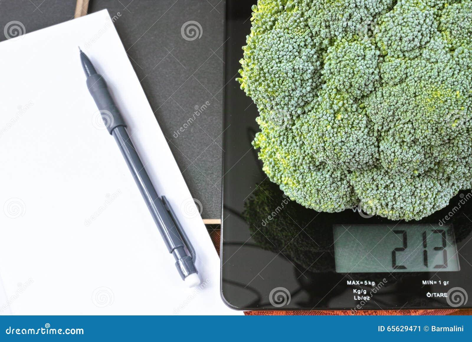 Surveillance du poids - échelle en verre noire de cuisine avec le brocoli, le crayon et le papier verts