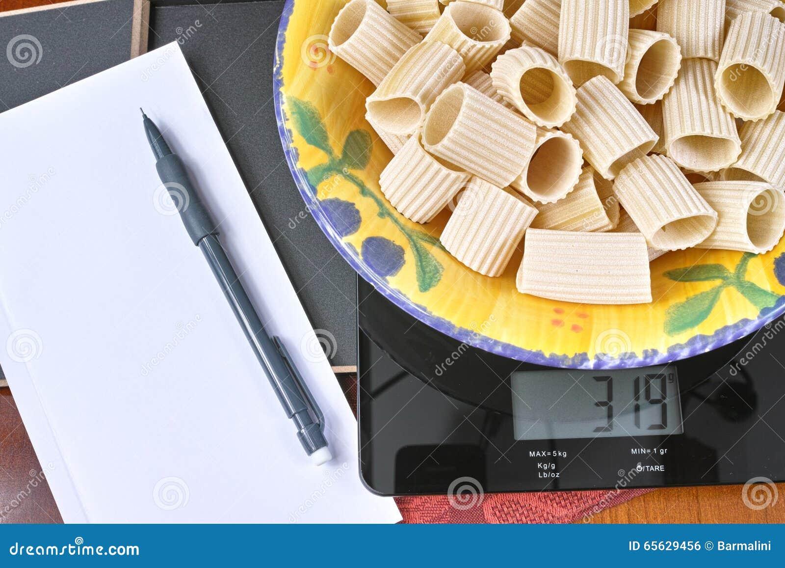 Surveillance du poids - échelle en verre noire de cuisine avec les pâtes, le crayon et le papier italiens