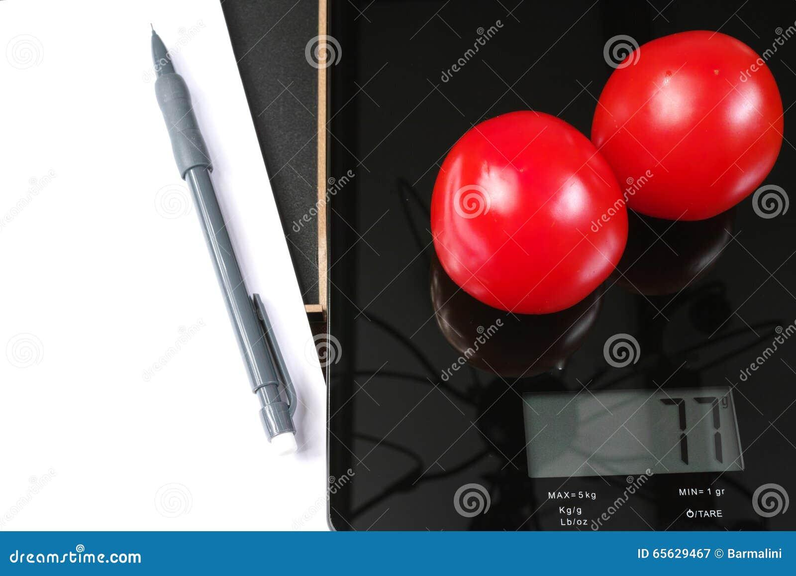 Surveillance du poids - échelle en verre noire de cuisine avec les tomates, le crayon et le papier rouges