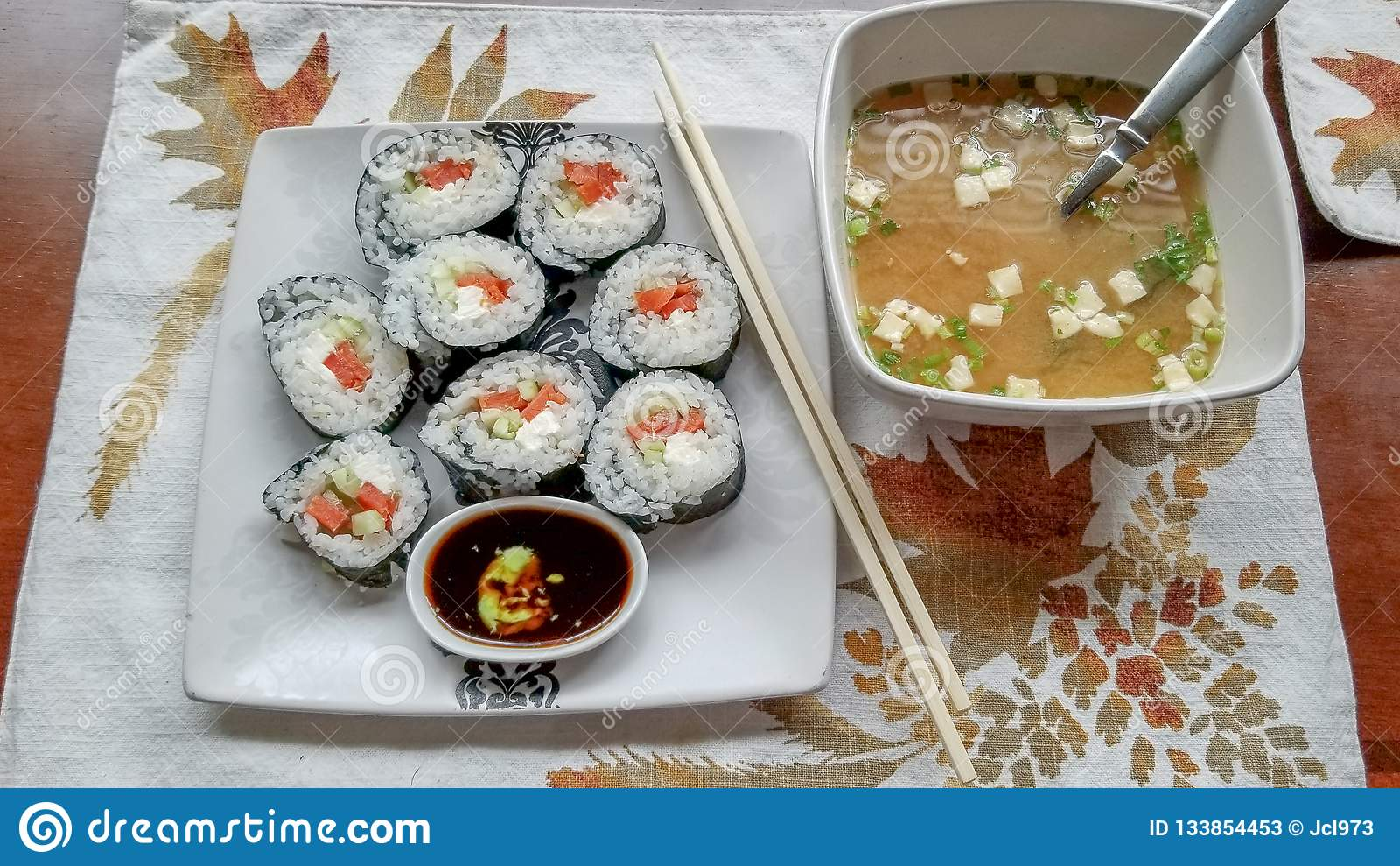 Sushi die in zeewier worden verpakt en die met gerookte zalm, roomkaas en komkommer, met kleine onderdompelende kom van sojasaus
