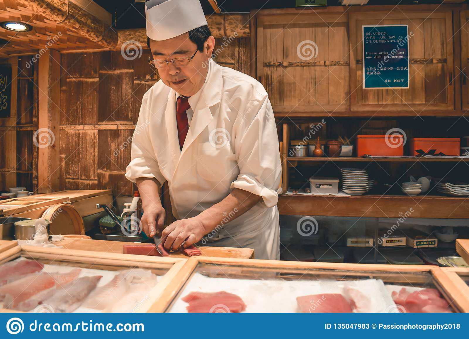 Sushi hoofdchef-kok die het verse ontbijt van de tonijnsashimi voorbereiden bij de Tsukiji-vissenmarkt in Tokyo