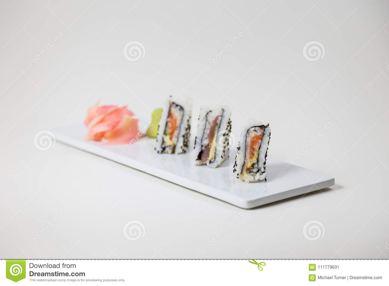 Sushi on a white plate on a white background and pickled ginger