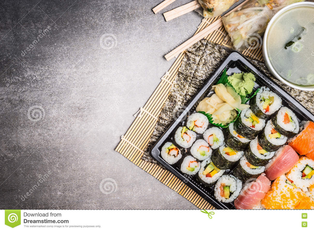 Sushi menu with summer rolls, nigiri , soy sauce and miso soup on gray stone background, top view, place for text