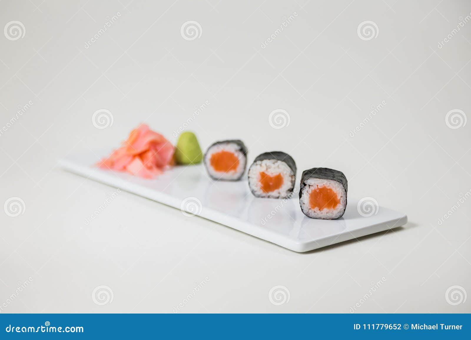 Sushi på en vit platta på en isolerad vit bakgrund