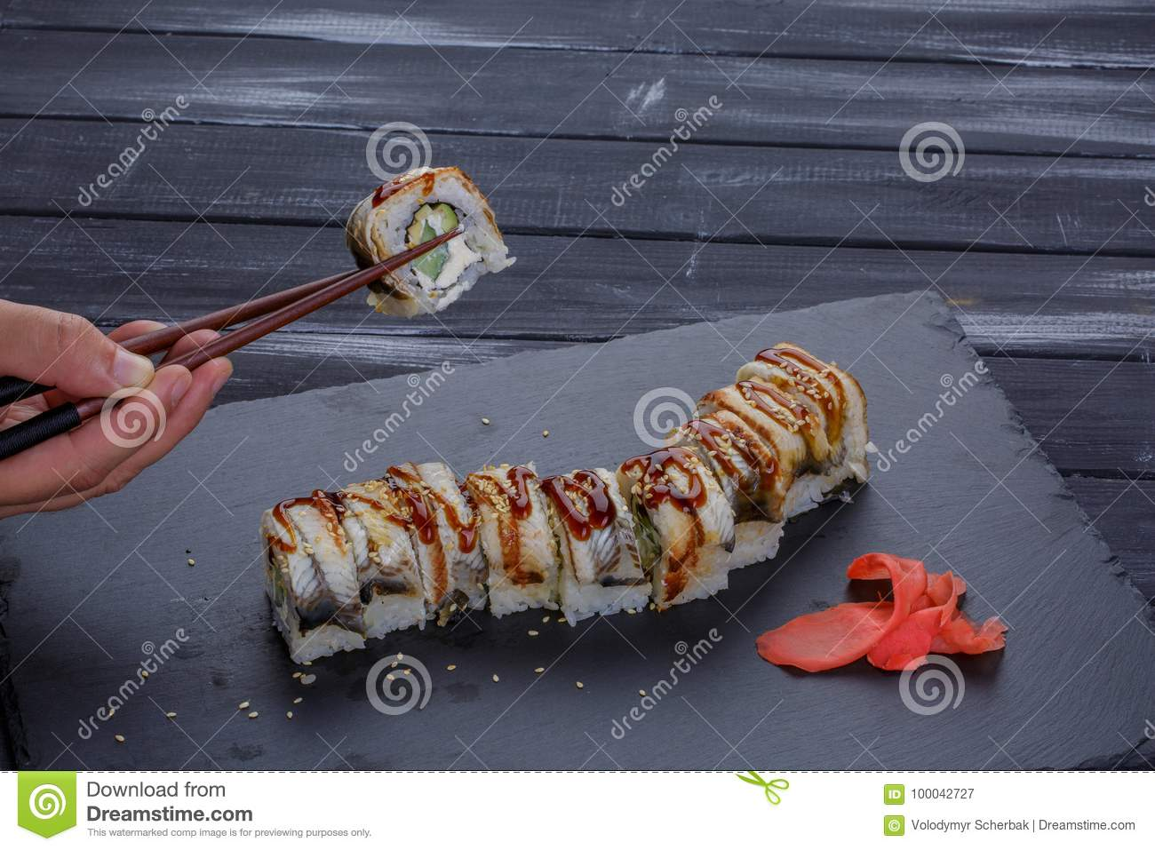 Sushi - Roll on a black plate with man hand holding chopsticks over black background