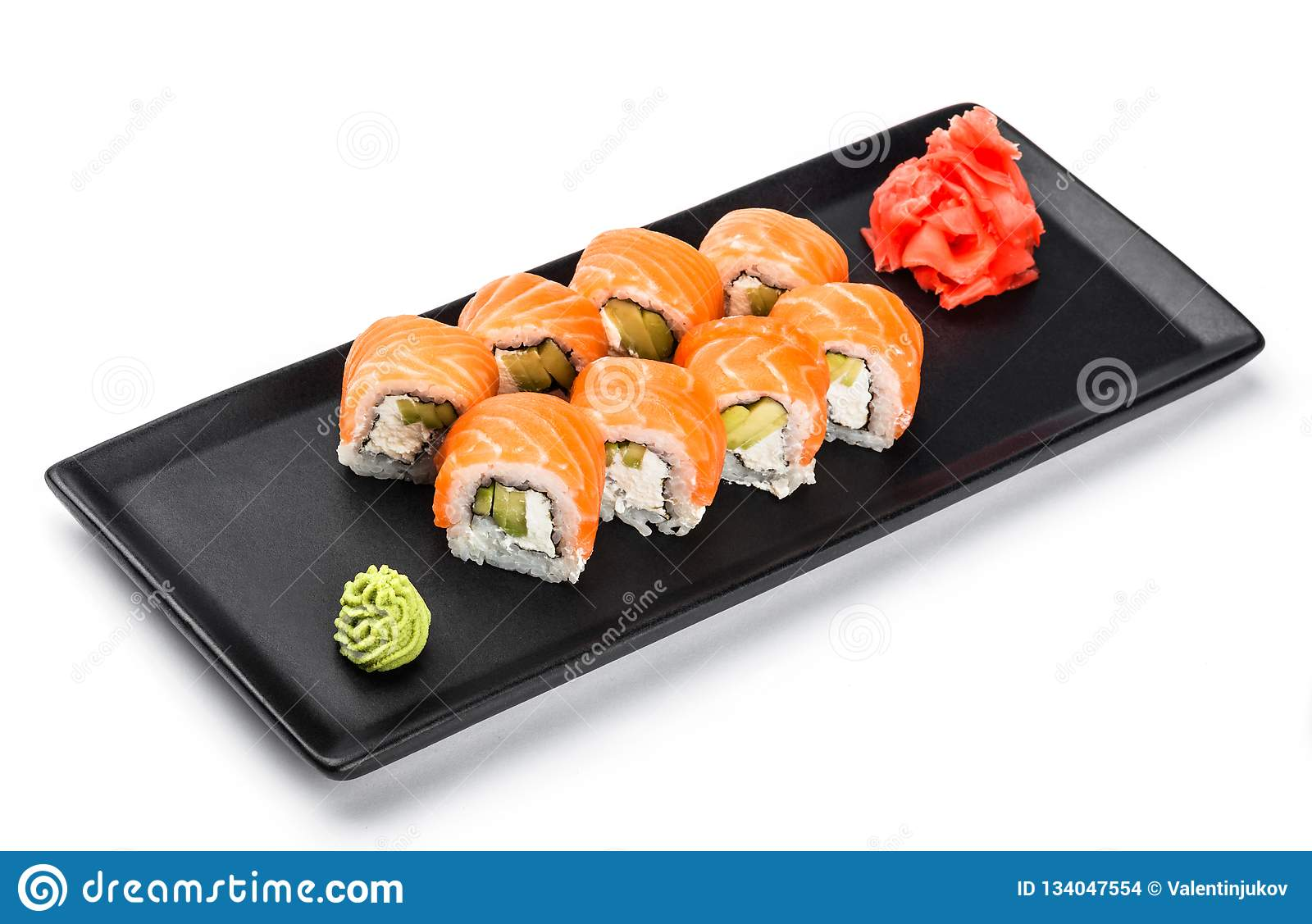 Sushi Roll - Maki Sushi made of salmon, avocado and cream cheese on black plate isolated over white background.