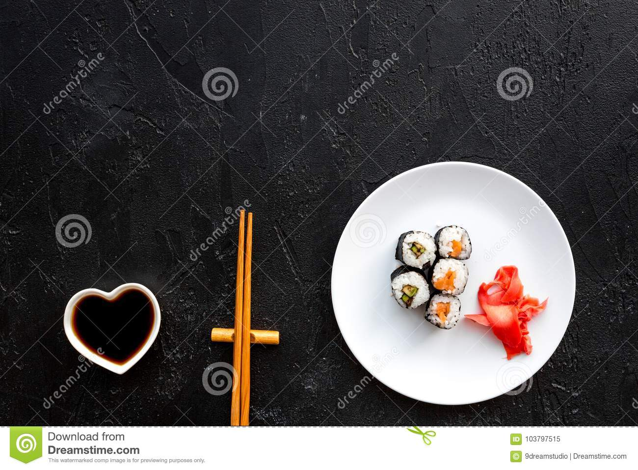 Sushi roll with salmon and avocado on plate with soy sauce, chopstick, wasabi on black background top view copyspace