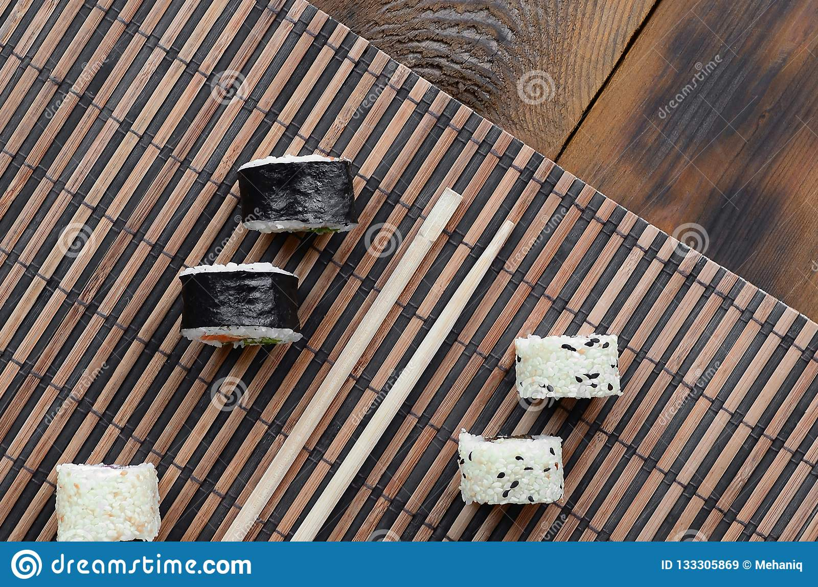 Sushi rolls and wooden chopsticks lie on a bamboo straw serwing mat. Traditional Asian food. Top view
