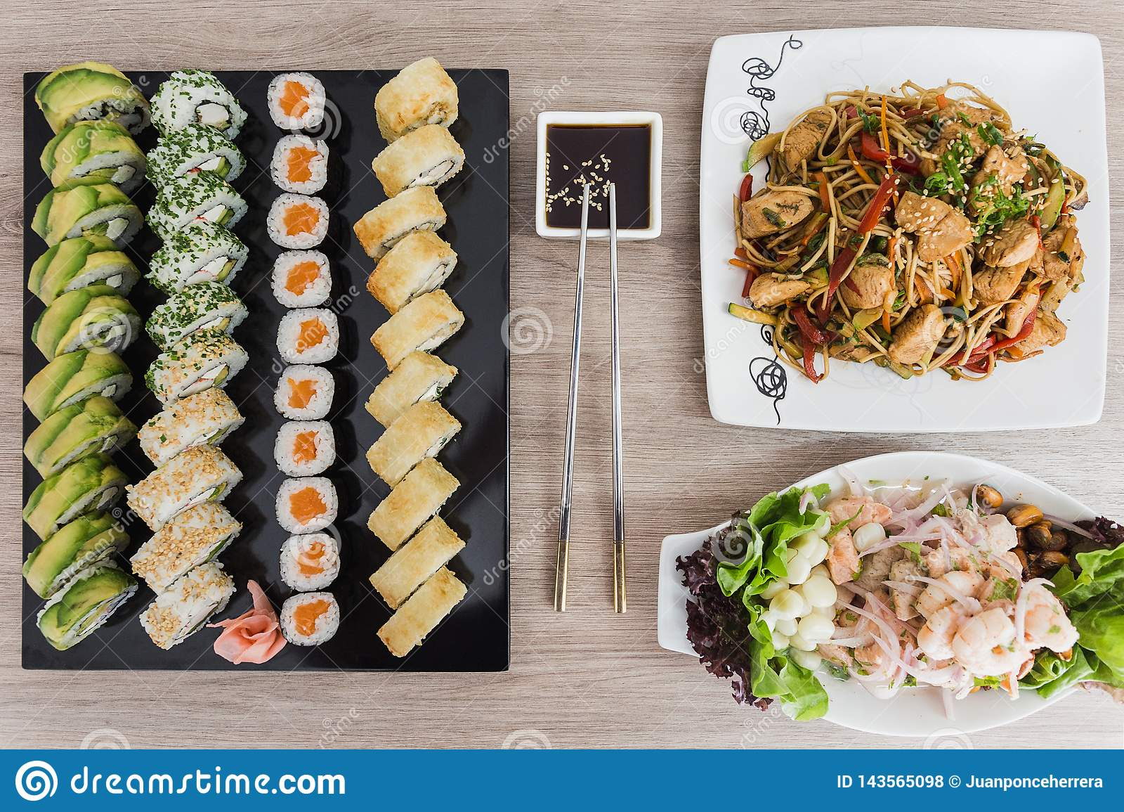 Sushi rolls with yakisoba, ceviche and soy sauce on a wooden table