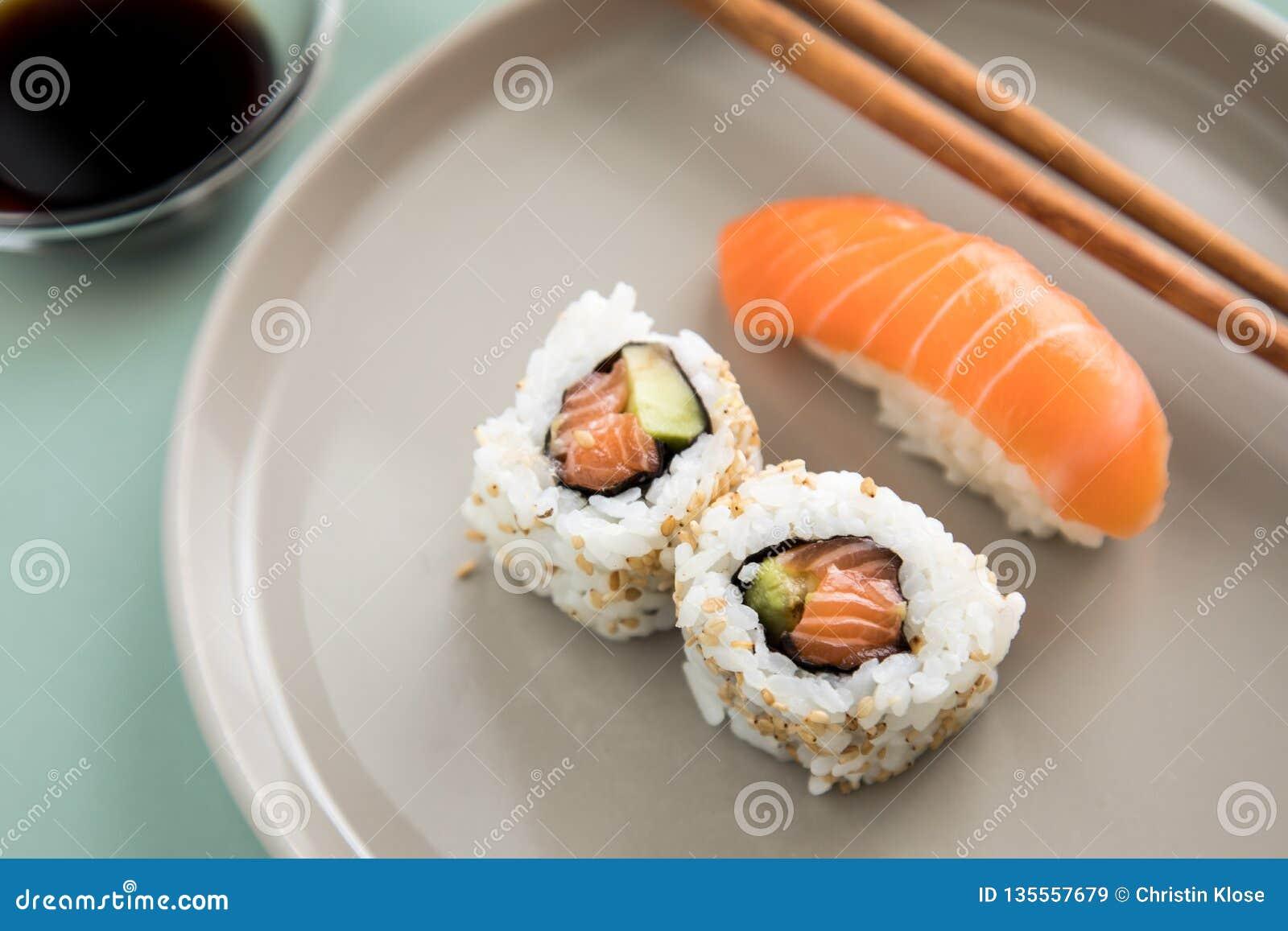Sushi saumonés japonais de Nigiri et à l envers de Californie avec l avocat, la sauce de soja et les baguettes en bois du plat de