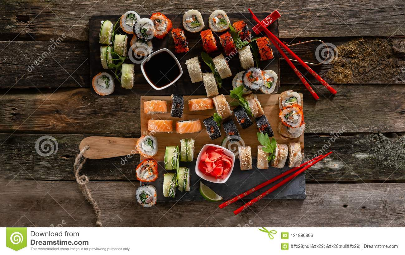 Sushi set food photo. Rolls served on brown wooden and slate plate. Close up and top view of sushi. 16 in 9 crop