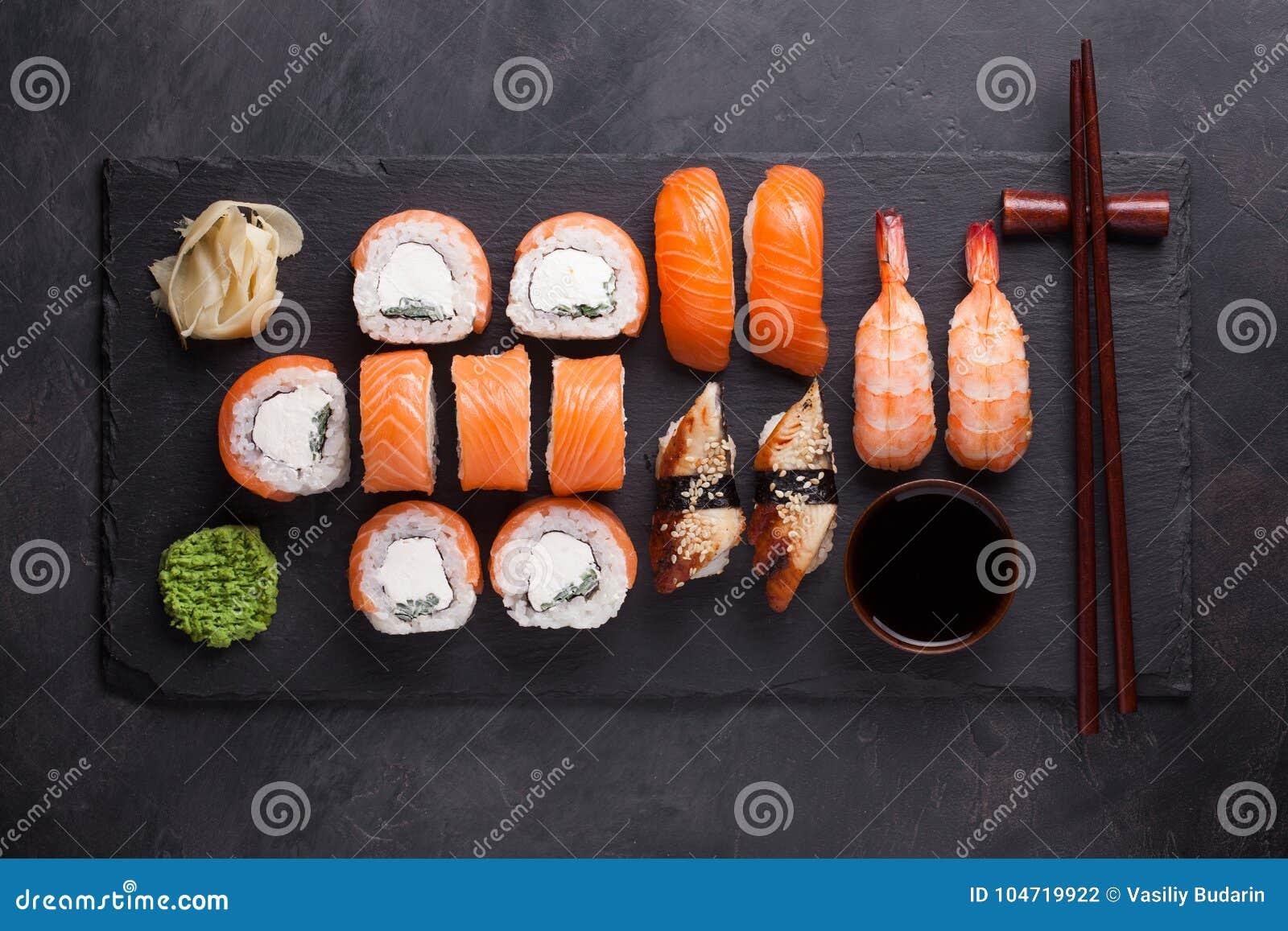 Sushi Set sashimi with salmon, shrimp, eel and sushi rolls philadelphia served on stone slate. Top view