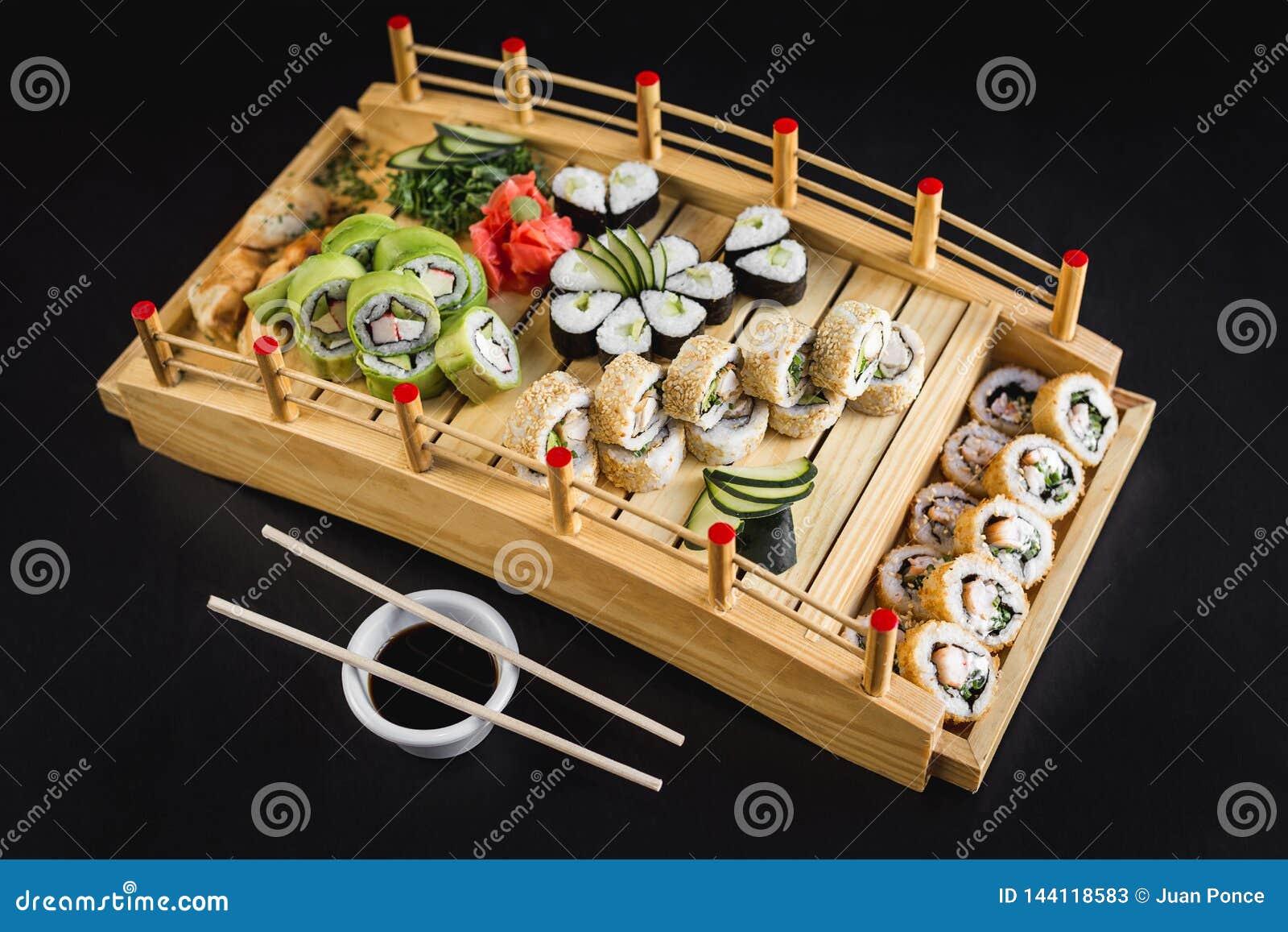 Sushi table with california, avocado, hosomaki and tempura rolls on a wooden table