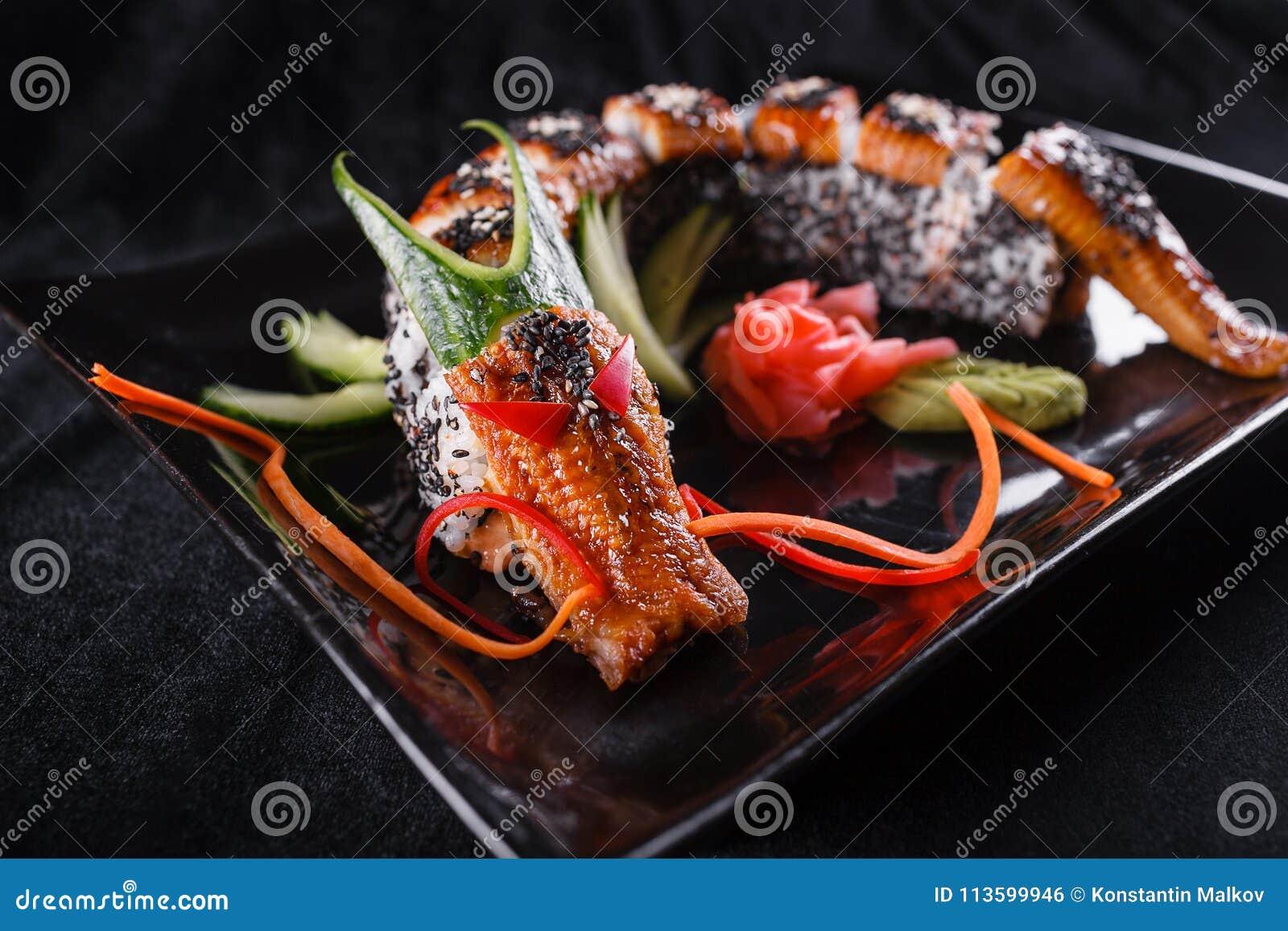 Sushidrache mit Aal, Gurke und Avocado auf einem schwarzen Hintergrund Japanisches Lebensmittel, geschmackvoll von der Mahlzeit f