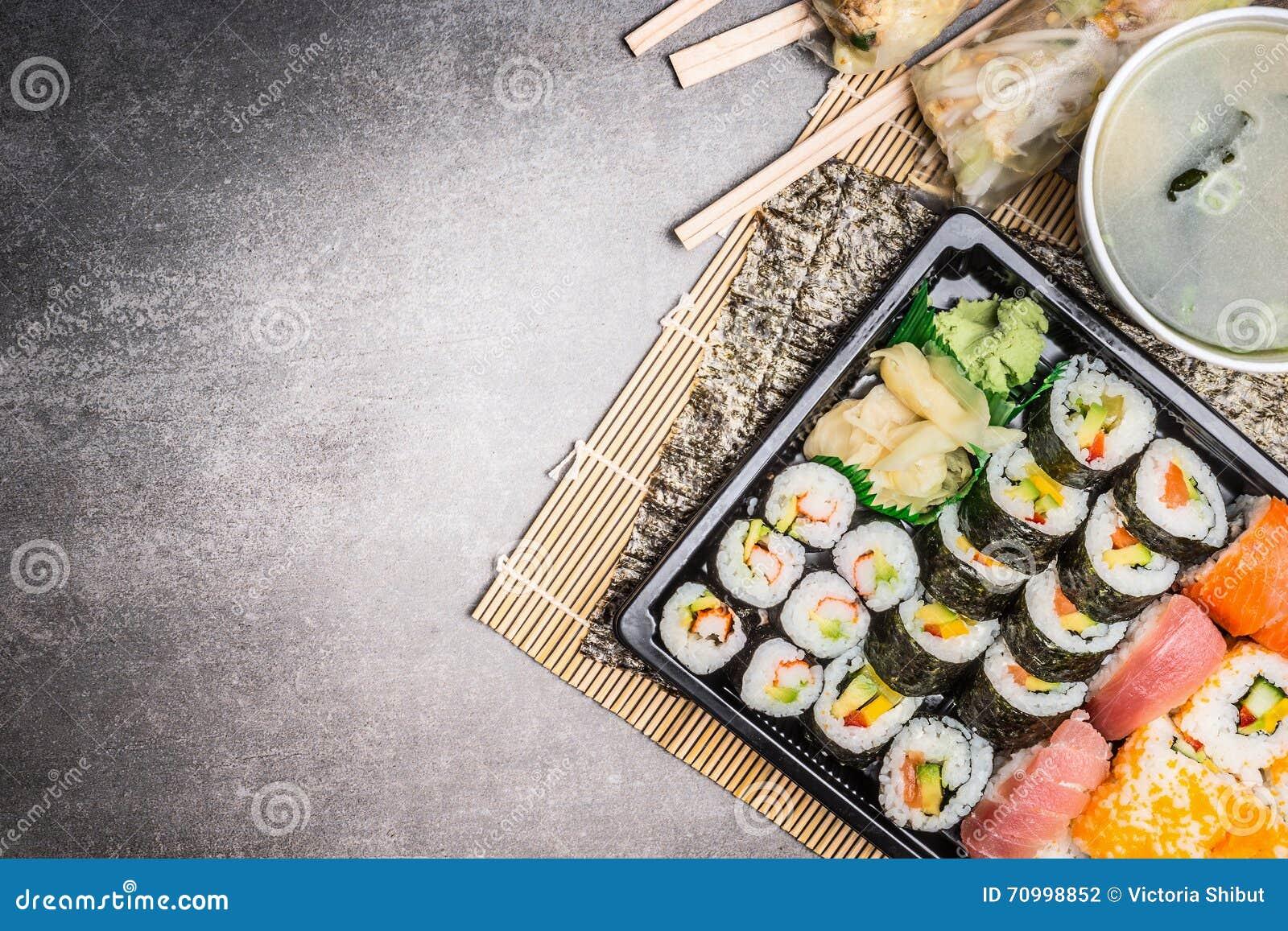 Sushimenyn med sommarrullar, nigirien, soya och misosoppa på grå färger stenar bakgrund, den bästa sikten, stället för text