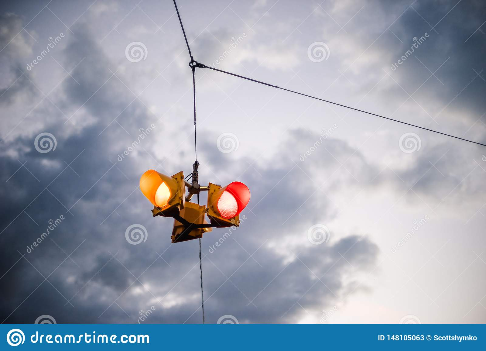 A suspended traffic signal against a moody sky