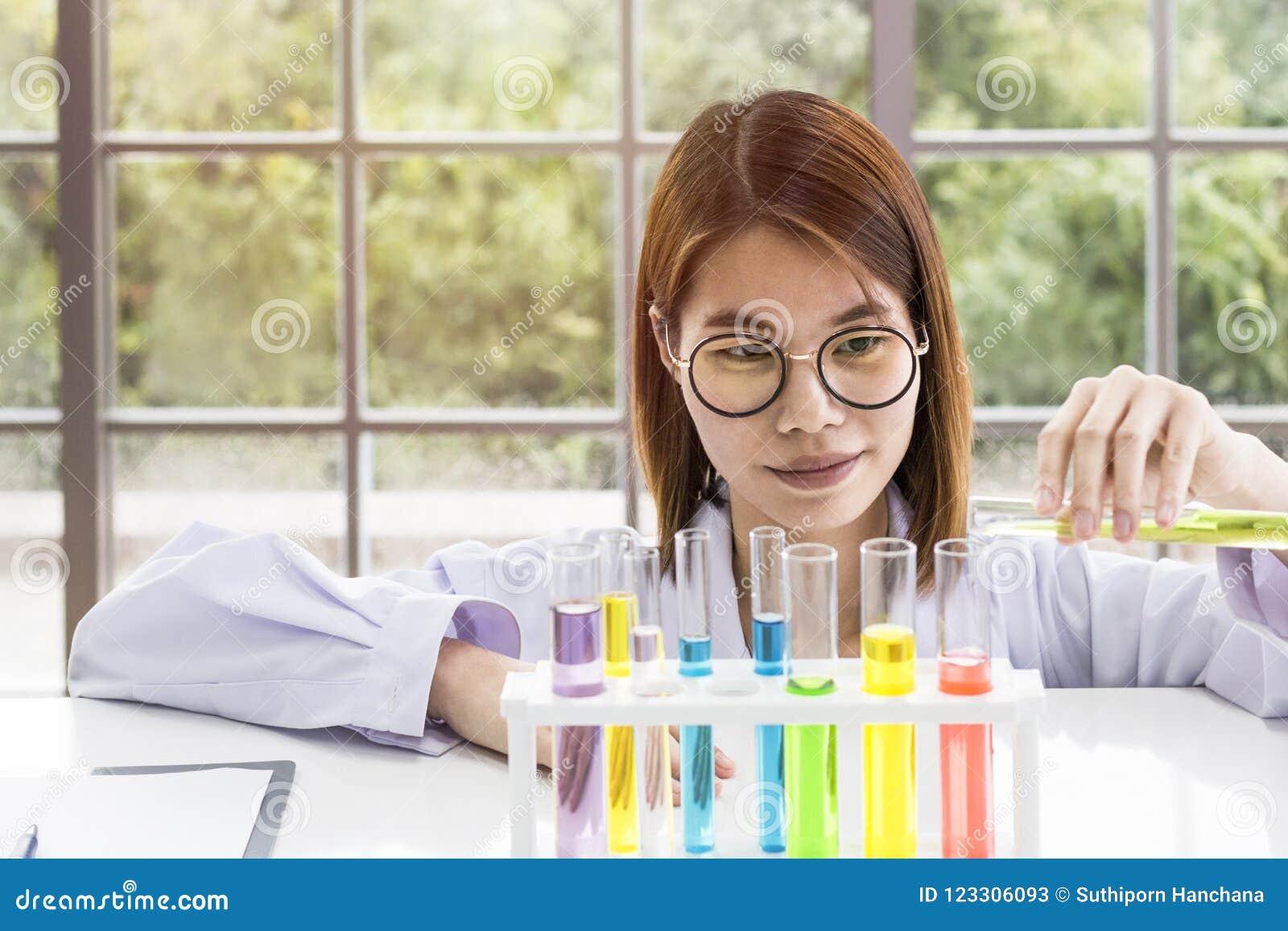 Sustancias de mezcla del estudiante femenino joven del científico en tubo de ensayo