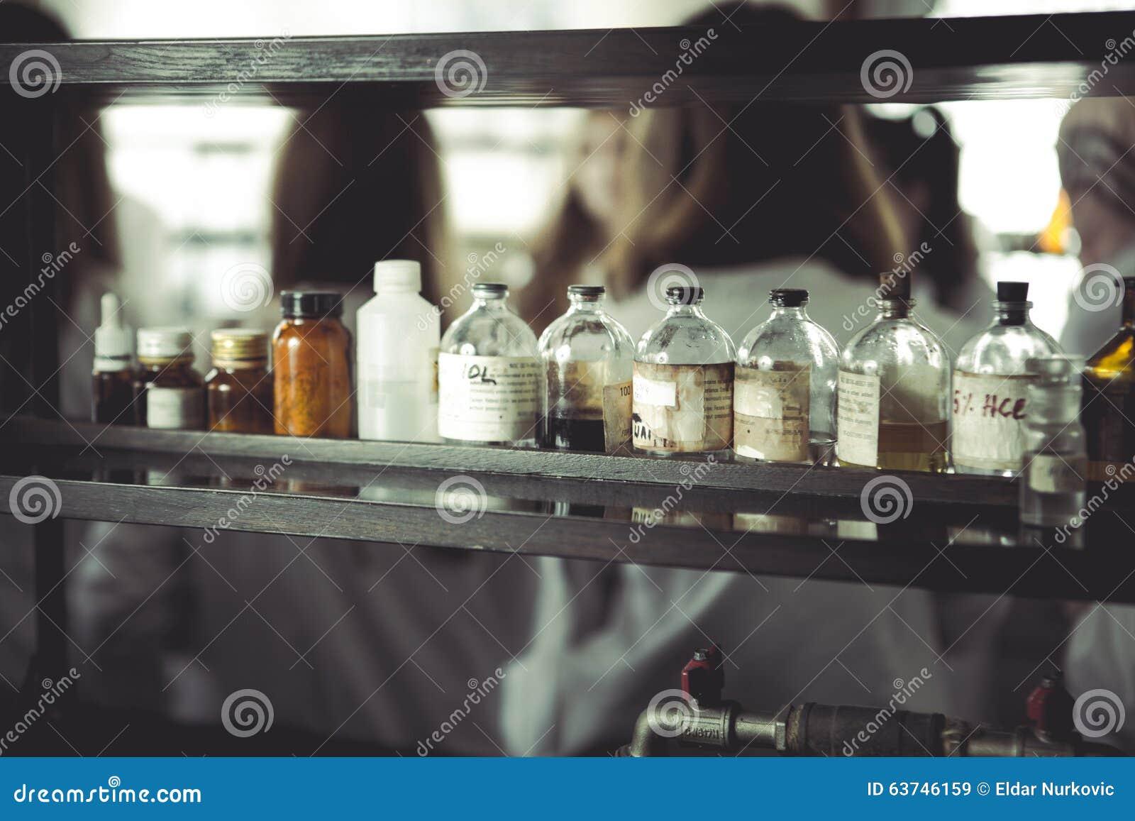 Sustancias químicas y utensilios del laboratorio botellas de la farmacia del vintage en el tablero de madera Botellas químicas pa