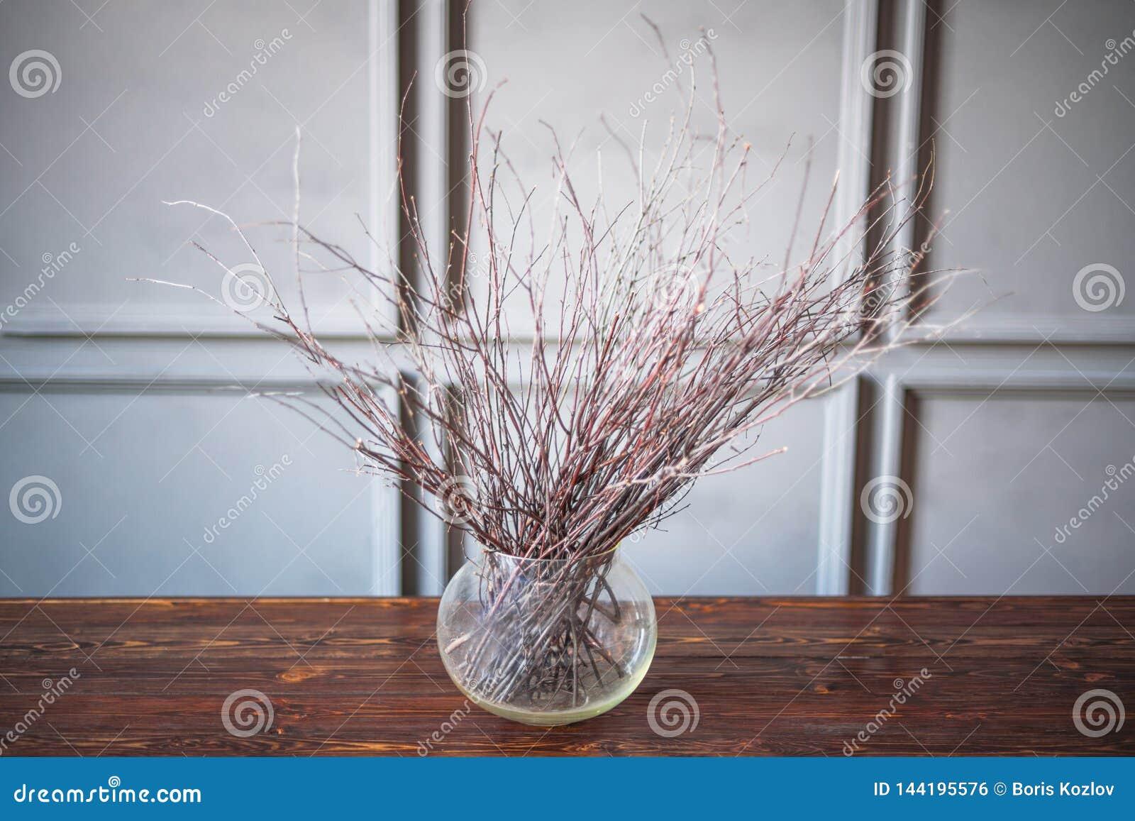 Suszy gałąź w przejrzystej wazie na drewnianym stole, szary tło