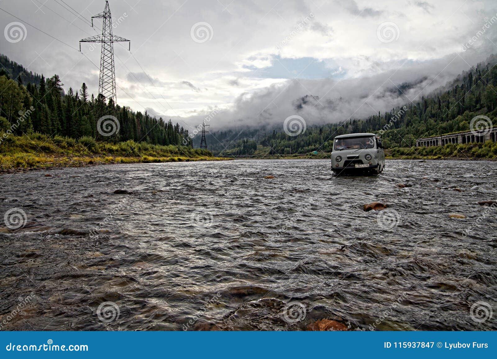 SUV grigio russo attraversa il fiume della montagna con le linee elettriche sulla riva sinistra e su una linea ferroviaria sulla