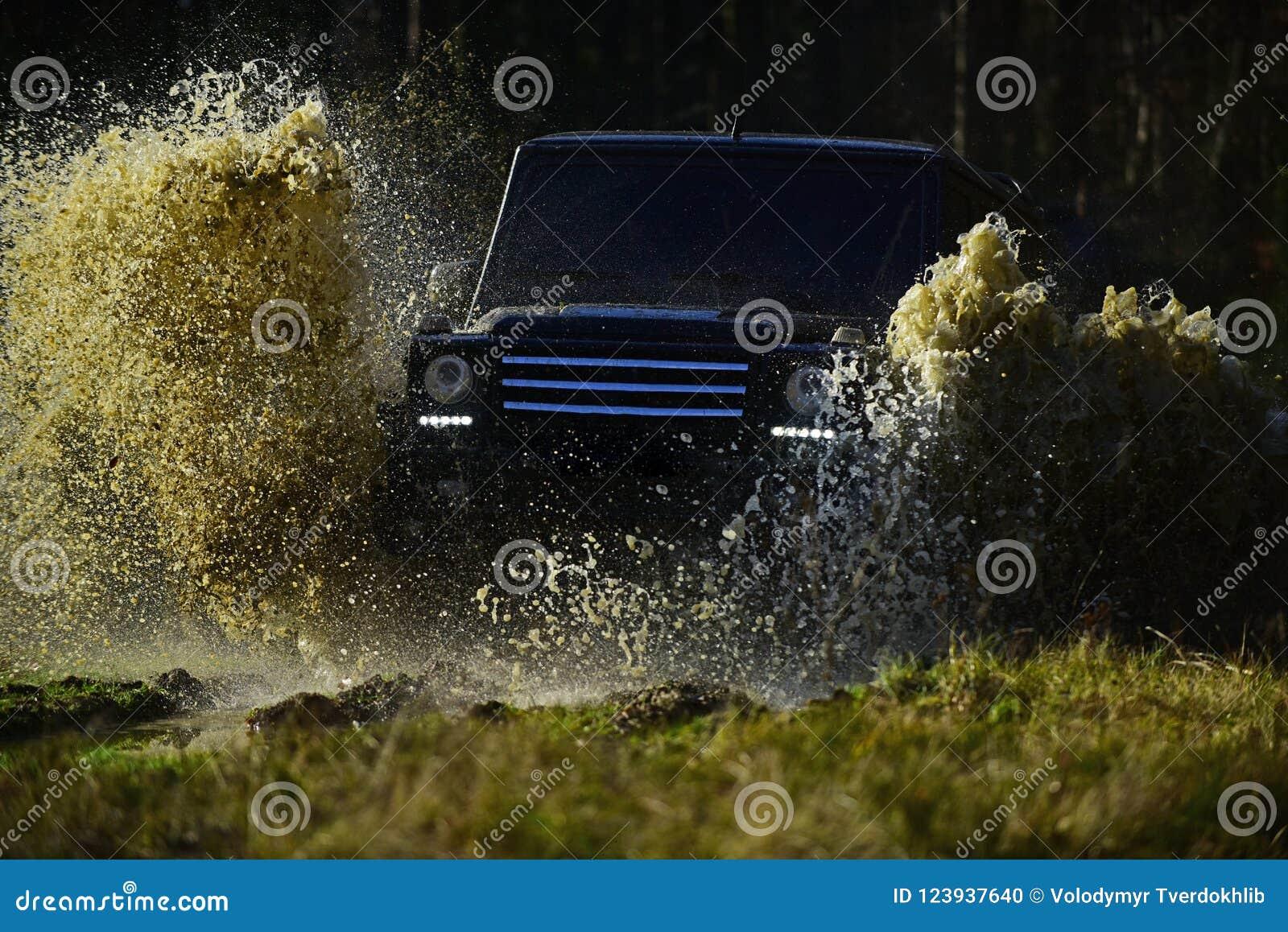 SUV oder Auto nicht für den Straßenverkehr auf dem Weg bedeckt mit Grasüberfahrtpfütze mit Schmutzwasserspritzen Extrem, Herausfo
