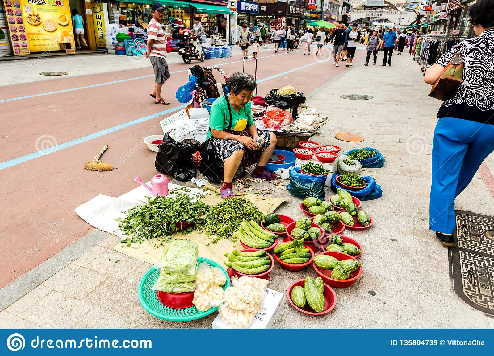 Suwon, South Korea - June 25, 2017: Vendor woman selling vegetables and fruits in the street market at downtown in Suwon