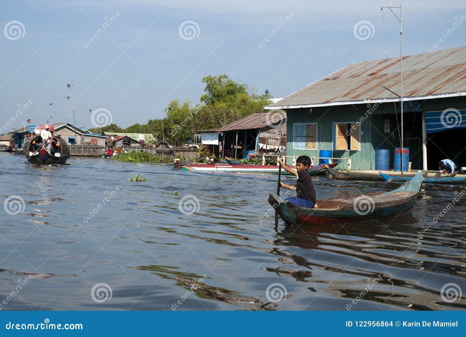 Sväva byn, pojke i kanot som navigerar flodtrafiken