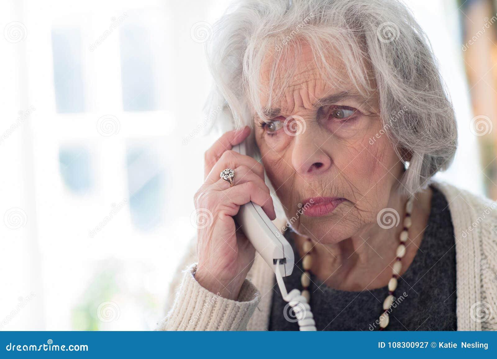 Svarande telefon för bekymrad hög kvinna hemma