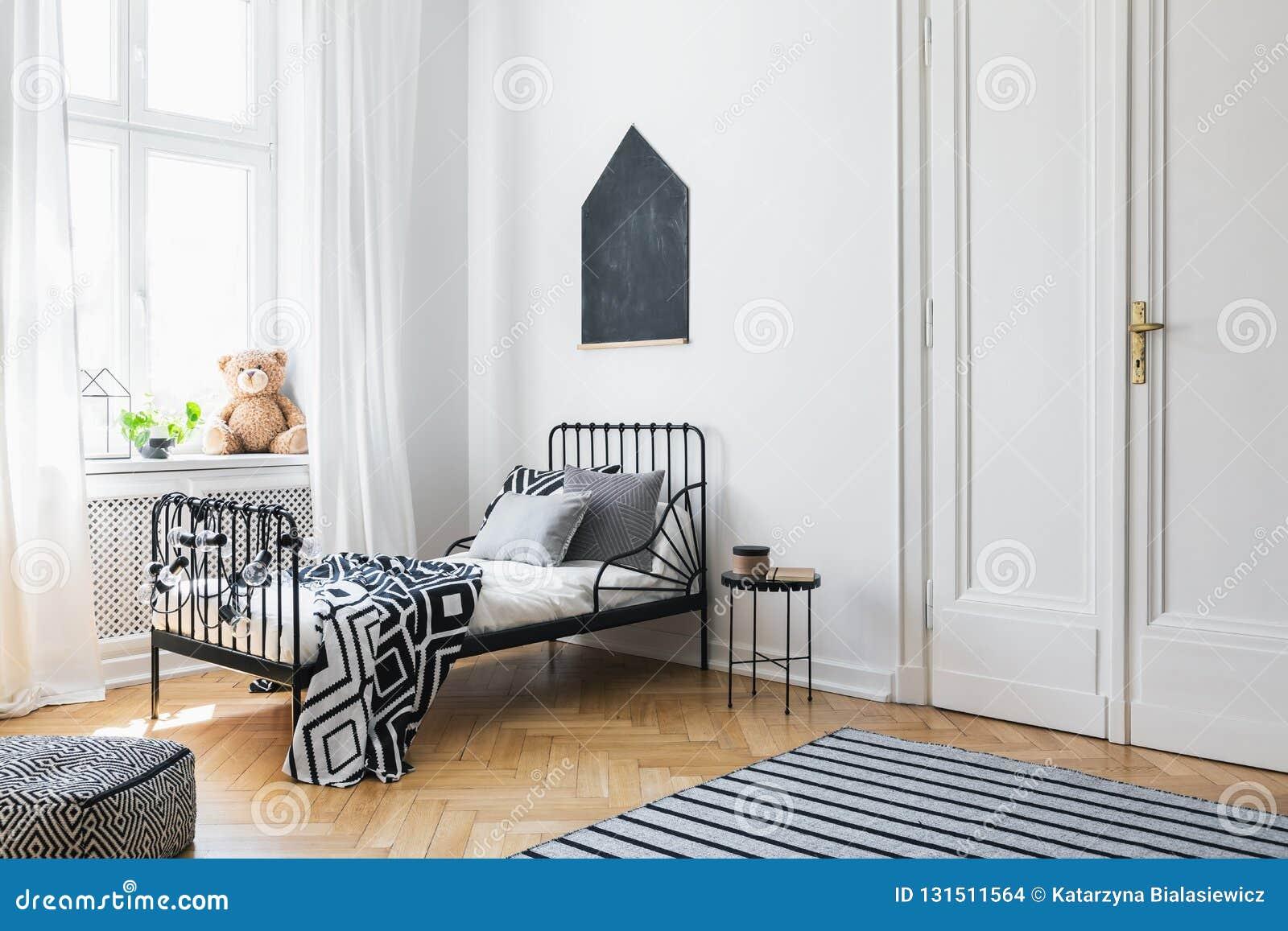 Svart affisch ovanför säng med mönstrade ark