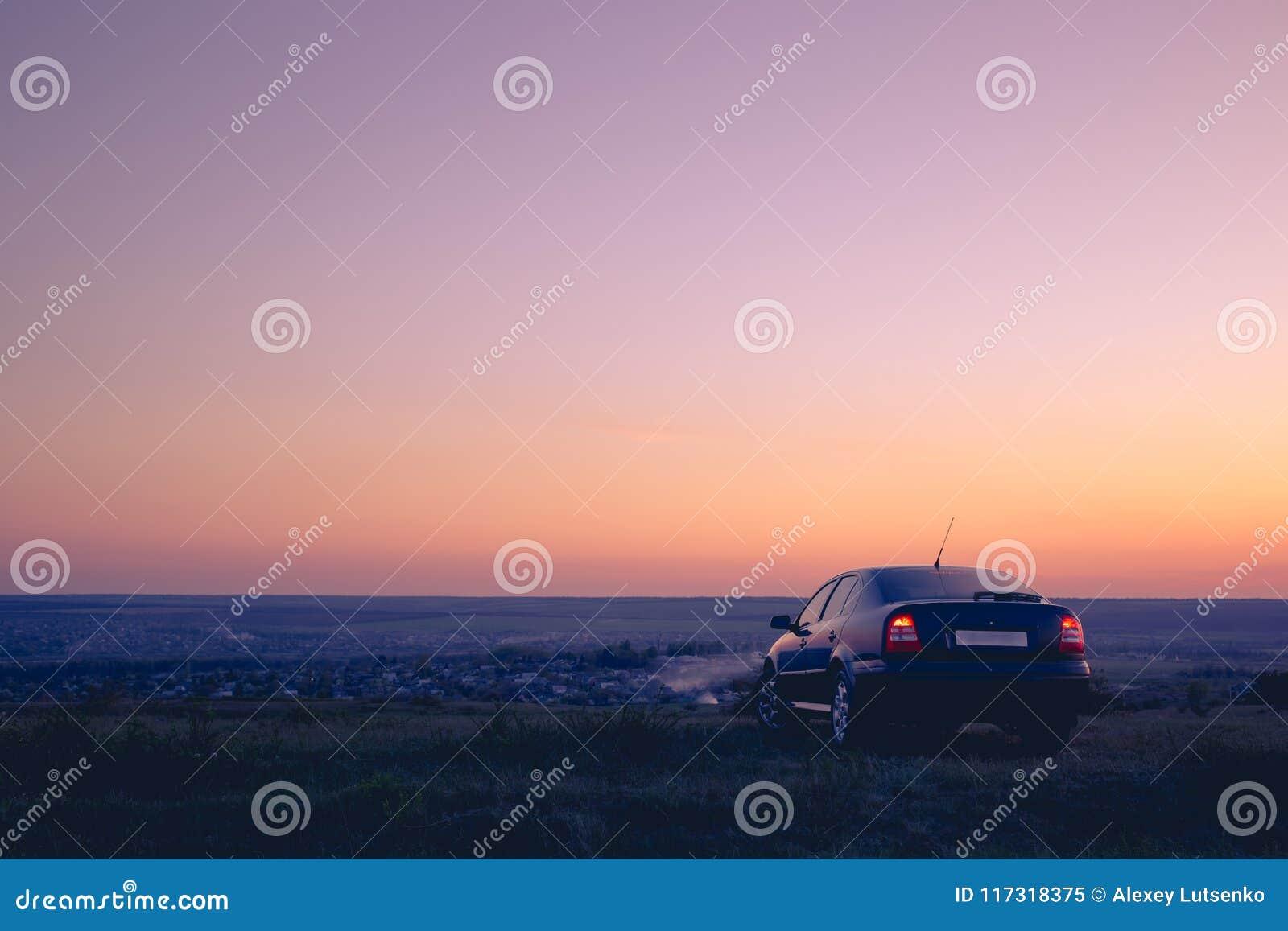 Svart bil i fältet på solnedgången
