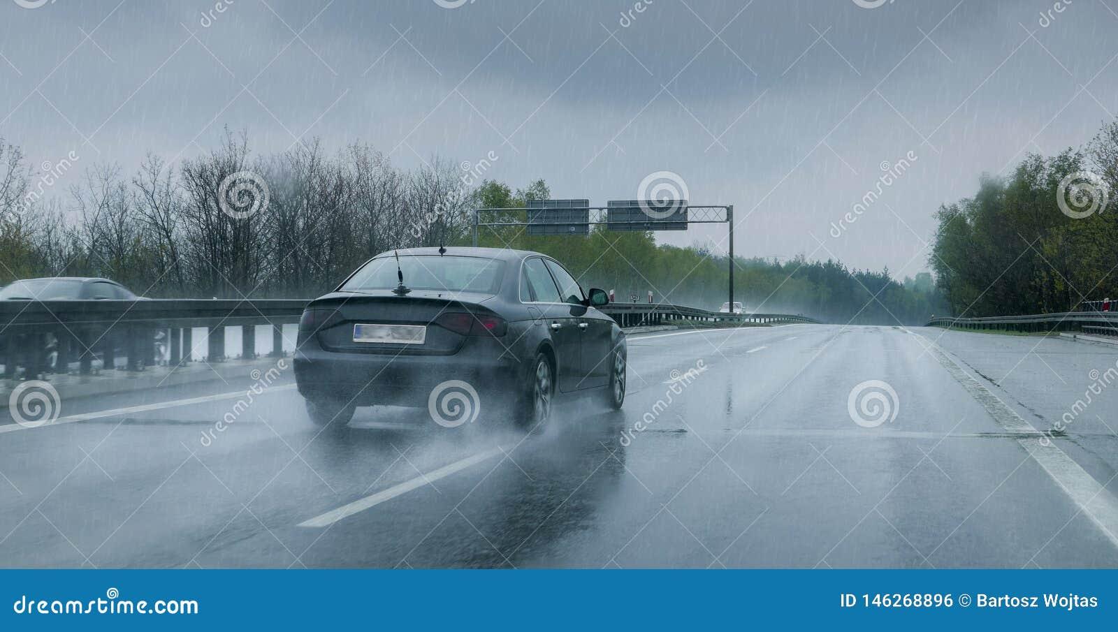 Svart bil som reser till och med h?llregn p? huvudv?gen
