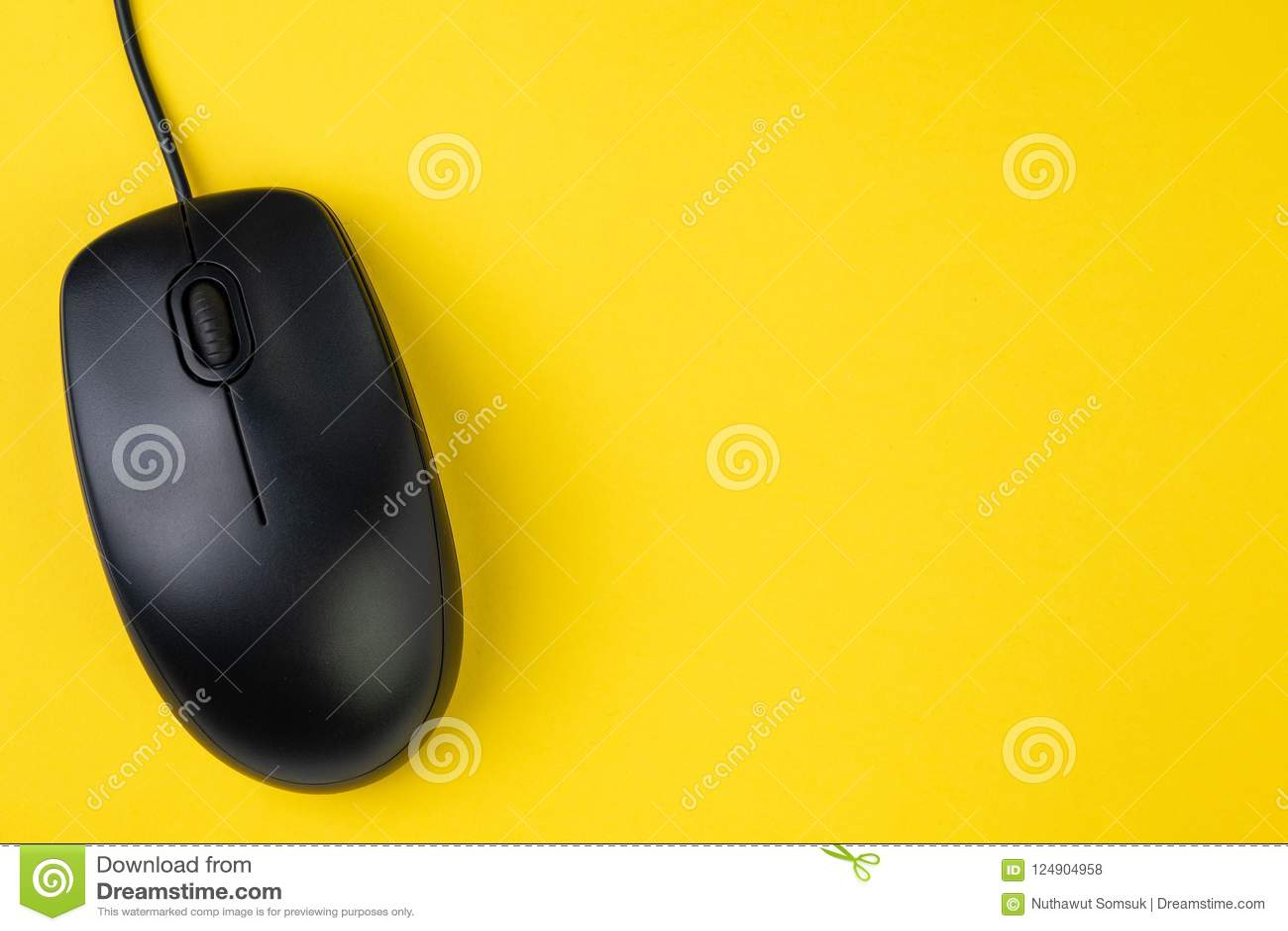Svart datormus med snirkelhjulet och kabel på den gula tabellen