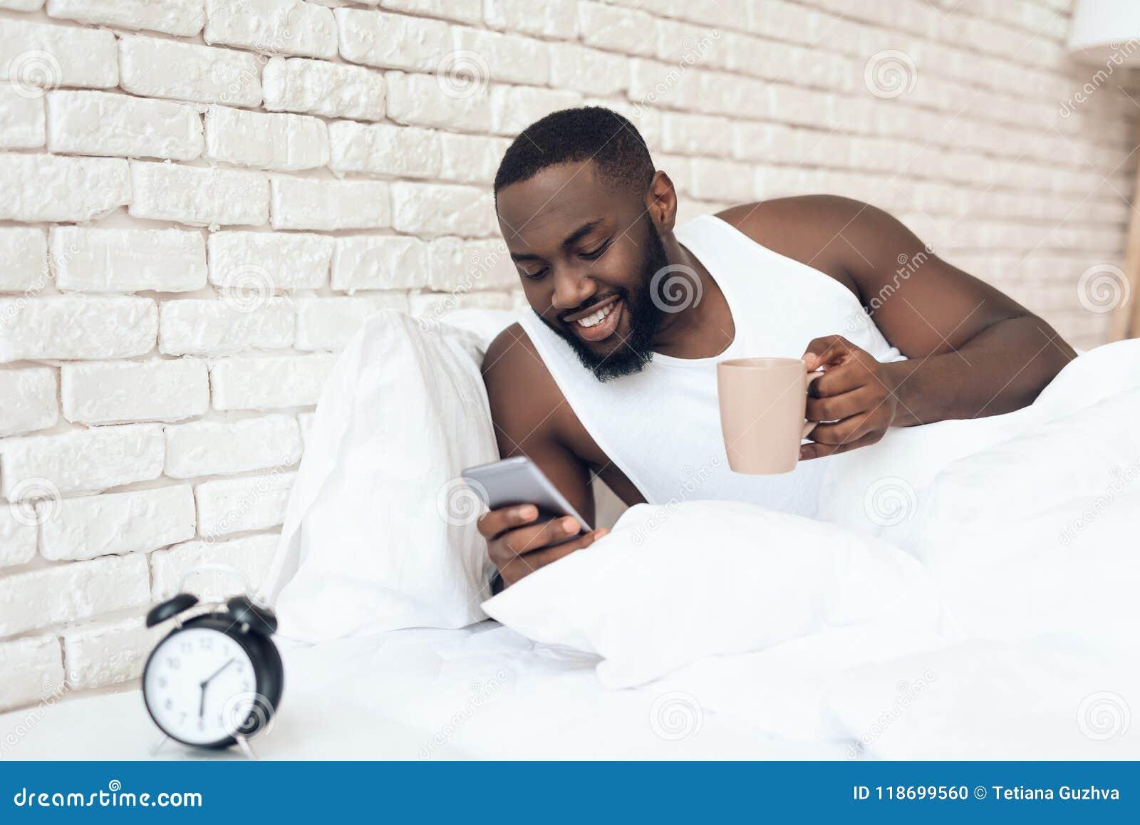 Svart den väckte mannen dricker kaffe, i att bläddra för säng