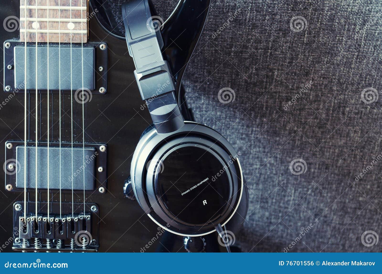 Svart elektrisk gitarr och hörlurar